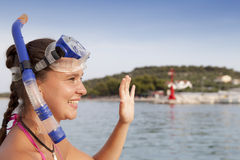Lovely girl at the seaside wearing a diving mask and waving hello Royalty Free Stock Images