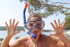 Lovely girl at the seaside wearing a diving mask and waving hello Stock Photography