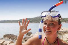 Lovely girl at the seaside wearing a diving mask and waving hello Stock Photo