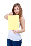 Lovely girl shows a blank A4 sheet of yellow Stock Photography