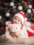 Lovely girl sitting on the floor near the Christmas tree with a bear, studio shot, toning in vintage style. Royalty Free Stock Image