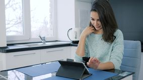 Lovely girl sitting on Internet using tablet while drinking tea in morning. In kitchen stock footage