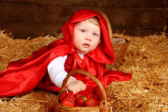 Lovely girl is sitting on pile of straw with a basket. Little Re Royalty Free Stock Image