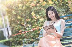 Lovely girl is sitting and playing tablet Royalty Free Stock Photo