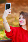 Lovely girl with smartphone taking selfie photo. Stock Photos