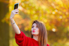 Lovely girl with smartphone taking selfie photo. Royalty Free Stock Photo