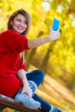 Lovely girl with smartphone taking selfie photo. Royalty Free Stock Photos