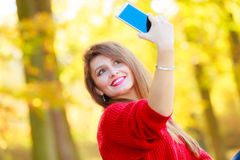 Lovely girl with smartphone taking selfie photo. Technology and fun concept. Enjoyable attractive girl playing with mobilephone. Cheerful gorgeous woman smiling Royalty Free Stock Photo