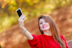 Lovely girl with smartphone taking selfie photo. Technology and fun concept. Enjoyable attractive girl playing with mobilephone. Cheerful gorgeous woman smiling Stock Photos