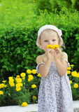 Lovely girl sniffing yellow flowers Royalty Free Stock Photos