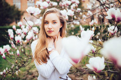 Lovely girl standing near Magnolia blossoming flowers, stands in white pink dress a small smile smiling Stock Image
