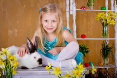 The lovely  girl is stroking an easter rabbit. The lovely fair-haired girl is stroking an easter rabbit next to narcissus Stock Photos