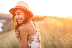 Lovely girl in stylish hat and summer dress smiling Royalty Free Stock Images