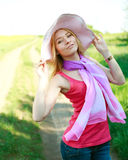 Lovely girl in a summer hat on a green glade Stock Image