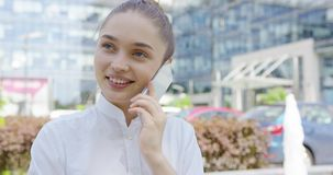 Lovely girl talking phone on urban background stock footage