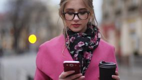 Lovely girl in a trendy look, standing in the city-center having a cup of coffee and texting message. Being busy. City. Lights on the background. Being online stock footage