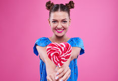Lovely girl with two buns showing a lollipop Royalty Free Stock Photos