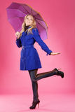 Lovely girl with an umbrella. Lovely woman in a blue coat with umbrella against pink background Stock Images