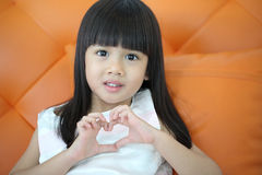 Lovely girl use hand cover and touch to make heart sign Stock Photo