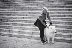 Lovely girl on a walk with a beautiful dog. Lovely girl on a walk with a beautiful fluffy dog Samoyedr Stock Photography