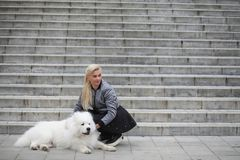 Lovely girl on a walk with a beautiful dog. Lovely girl on a walk with a beautiful fluffy dog Samoyedr Royalty Free Stock Photos