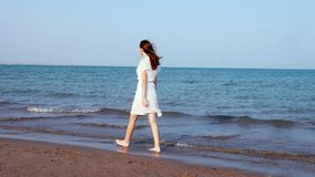 Lovely girl walking along the beach in white dress. Woman walking along beach in white dress stock video