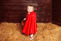Lovely girl walking on pile of straw with a basket. Little Red R Royalty Free Stock Photography