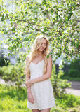 Lovely girl in white dress in summer. Enjoying warm sunny day, beautiful blonde on nature Royalty Free Stock Photo