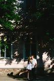 Lovely girl in white kissing her man in a cheek stock image