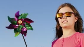 Lovely girl with windmill toy. Lovely girl in sunglasses with windmill toy on the blue sky background smiling and looking at the sunset stock video footage