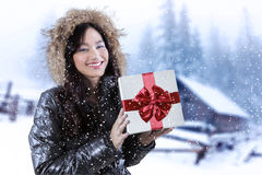 Lovely girl with winter jacket and gift box. Pretty teenage girl smiling happy while holding a gift box and wearing winter jacket Royalty Free Stock Photos