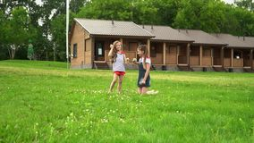 Lovely girls have fun on recreation facility. Summer mood at two beautiful little sisters. On this video you can see as two setra sit in the park on a lawn. On a stock video