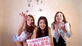 Three stylish female friends posing with sign chrismas sales and calling for shopping, stand in room against background. Lovely girls with smiles on their faces stock footage