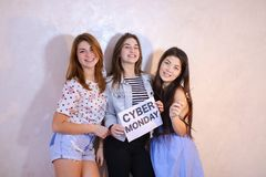 Three stylish female friends posing with sign and calling for sh royalty free stock image
