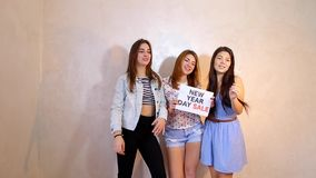 Three stylish female friends posing with sign New Year Sales and calling for shopping, stand in room against background. Lovely girls with smiles on their faces stock video