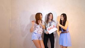 Three stylish female friends posing with sign Sale and calling for shopping, stand in room against background of light. Lovely girls with smiles on their faces stock video footage