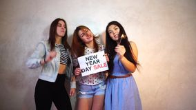 Three stylish female friends posing with sign and calling for shopping, stand in room against background of light wall. Lovely girls with smiles on their faces stock video