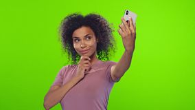 Glad black woman smiles broadly, takes selfie portrait on white cell phone