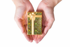 A lovely golden gift box with woman's hand. Royalty Free Stock Photo