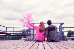 Lovely good-looking young couple spending time together on the wooden pier royalty free stock image