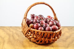 Lovely Gooseberry. Gooseberries in  a wickerwork plaited basket on a wooden table before a white background Royalty Free Stock Photography