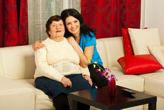 Lovely grandma and granddaughter home. Lovely grandma and her granddaughter sitting in a hug on couch  home Stock Photography