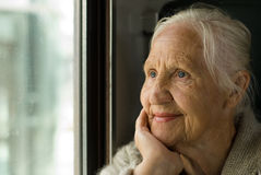 Lovely grandmother. Looking in a window, in a train Stock Photo