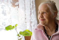 Lovely grandmother. Looking in the window Royalty Free Stock Images