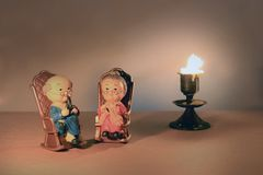 Lovely grandparent doll siting classic chair design and candle with light candle tone. low key lighting, still life style.  royalty free stock photo