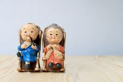 Lovely grandparent doll siting old sofa classic chair together on wooden table with background. Royalty Free Stock Photography