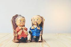 Lovely grandparent doll siting old sofa classic chair together on wooden table with background. stock photography