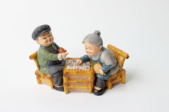 Lovely grandparent doll siting rocking bamboo chair with playing checkerboard. Royalty Free Stock Images