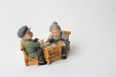 Lovely grandparent doll siting rocking bamboo chair with playing checkerboard. Stock Photos