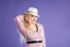 Beautiful young woman in sun hat on purple background royalty free stock image